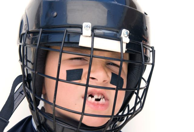 A young boy shows off his missing teeth while in his hockey gear.