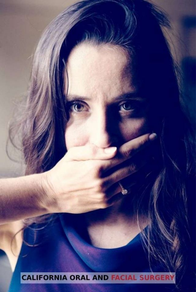 Woman covering her mouth with hand because of bad breath - Alameda, CA