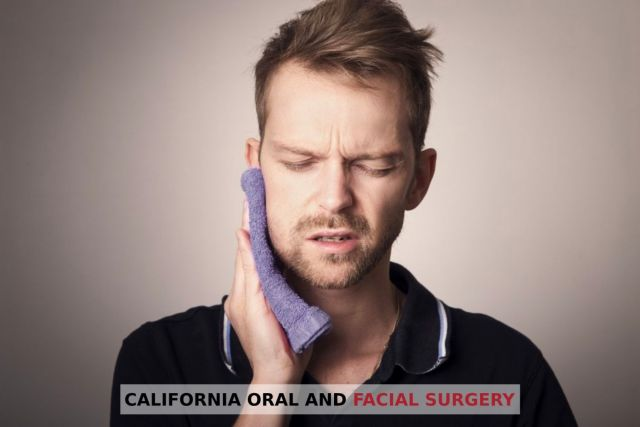Man holding towel to his face in pain because of facial fractures - Alameda, CA
